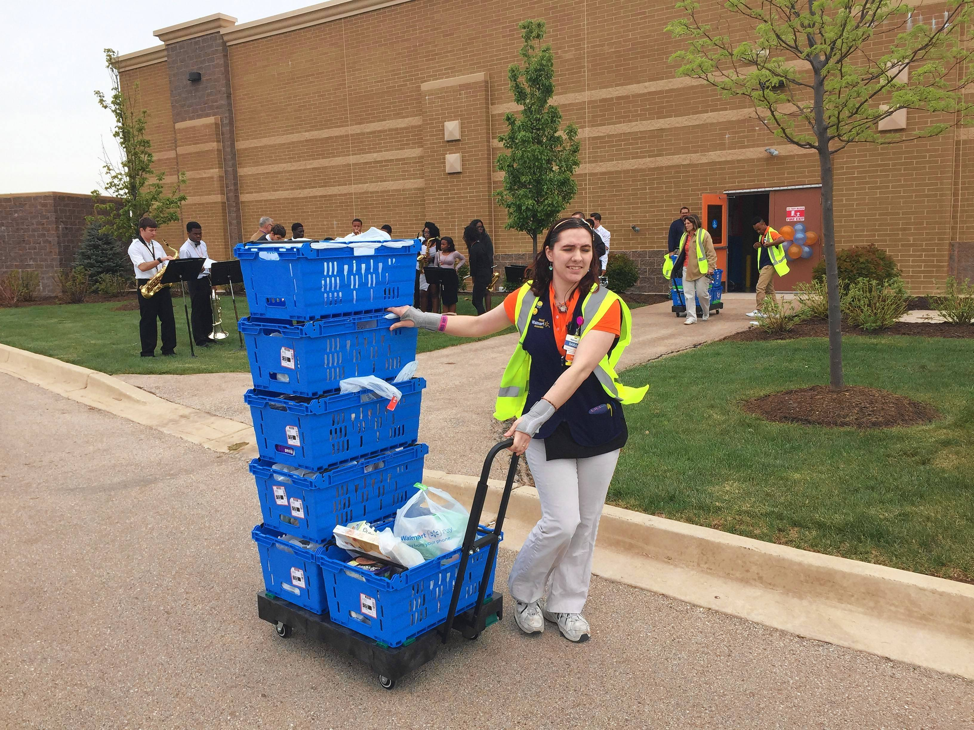Sarah Frew delivers groceries she picked to a customer's car Thursday at the Wal-Mart in Batavia. The store is one of several in the Chicago area that this week started offering free online grocery shopping with curbside pickup.