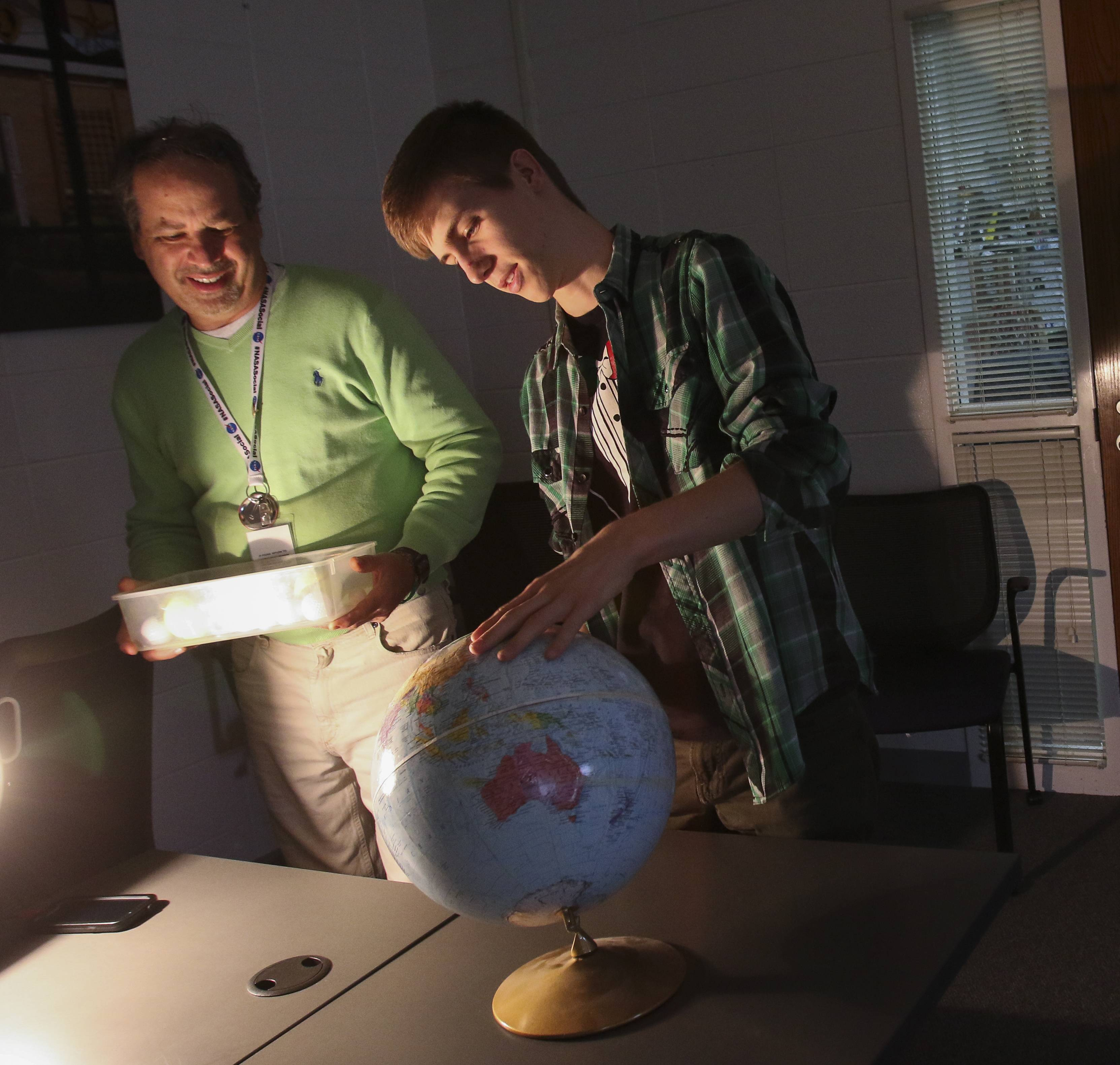 Charles Fulco, left, a NASA solar system ambassador, has Naperville North senior Robbie Plank demonstrate how an eclipse shadow falls on the earth in astronomy class on Thursday.