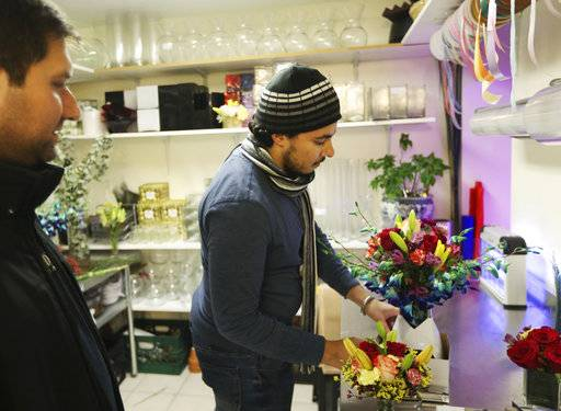 FILE - In this Nov. 30, 2016, file photo, Youssef Hassan, right, prepares a bouquet for Michael Levine at After Hours Flowers in New York. Small business owners have lost some of their post-election optimism, according to a survey released Thursday, May 4, 2017, by Wells Fargo & Co. (AP Photo/Seth Wenig, File)