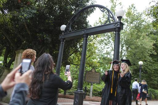 Soon-to-be graduates, Callie Rittweger, left, and Ashley Owen, right, from the University of Georgia's Franklin College of Arts communications program, pose for photos at the Arch, Thursday, May 04, 2017. The university will be having its graduation ceremony May 5 at Sanford Stadium. Georgia Governor Nathan Deal signed legislation allowing guns on Georgia's college campuses today also. (John Roark/ Athens Banner-Herald via AP)