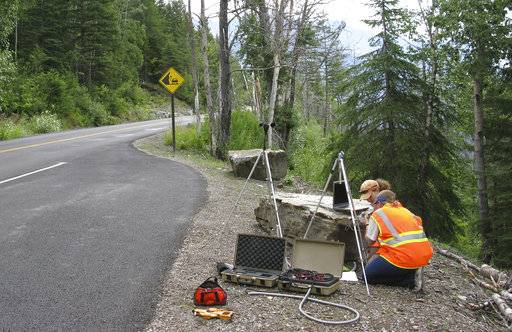 In this photo provided by the National Park Service a National Park Service staffer sets up an acoustic recording station on Going-to-the-Sun Road to capture the impact of traffic on acoustic conditions in Glacier National Park, Mont. The call of the wild is getting harder to hear. Peaceful natural sounds, bird songs, rushing rivers and rustling grass, are being drowned out by human-made noise in nearly two-thirds of America's protected parks, forests and wilderness areas, a new study finds. (National Park Service via AP)