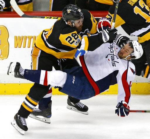 Pittsburgh Penguins' Ian Cole (28) checks Washington Capitals' Justin Williams (14) off the puck during the third period of Game 4 in an NHL Stanley Cup Eastern Conference semifinal hockey game in Pittsburgh, Wednesday, May 3, 2017. The Penguins won 3-2. (AP Photo/Gene J. Puskar)