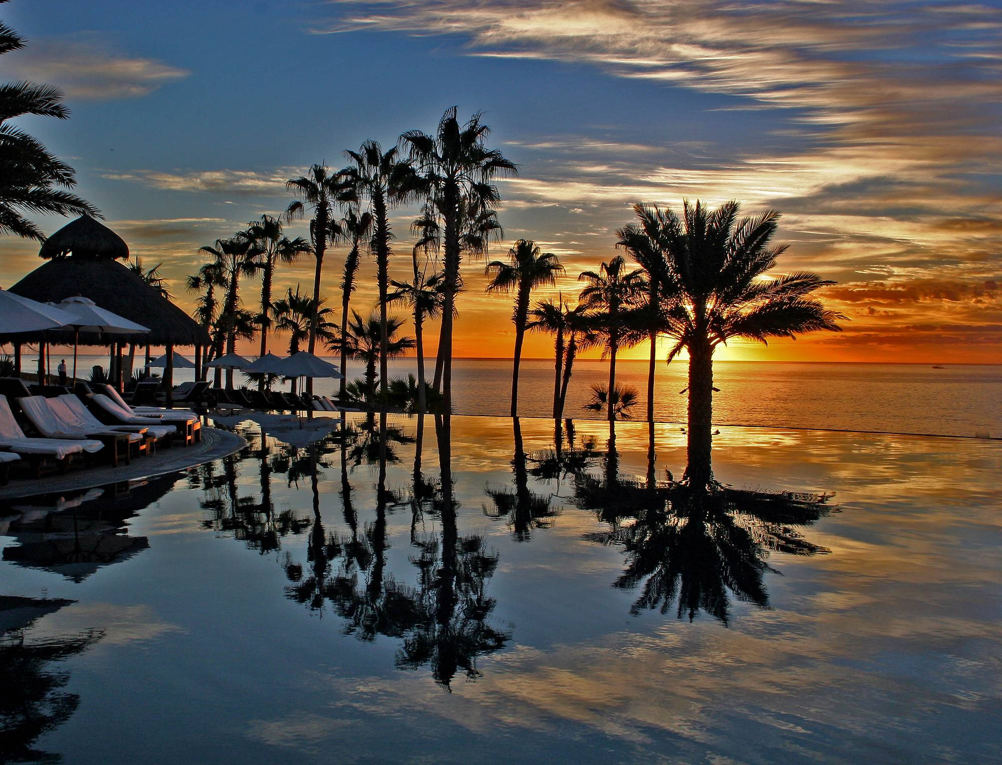 The Photo was taken on a colorful Morning in Cabo San Lucas, in an unique setting of an infinity swimming pool over looking the Sea of Cortez. There is double reflection. The golden colors of the sun and the distant sky reflected in the Sea of Cortez and distant part of the infinity pool. The palm trees and light golden clouds against a bluish sky reflected mainly in the infinity pool, making for a nice composition.