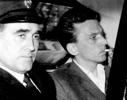 FILE - In this file photo dated Oct. 1965, Ian Brady, right, is escorted as he arrives at the courthouse in Hyde, Cheshire, England, to be convicted of the Moors murders of five children together with accomplice Myra Hindley in the Greater Manchester area of England. Brady has died Monday May 15, 2017, at a high security psychiatric hospital in Merseyside, England, according to Mersey Care NHS Foundation Trust. Myra Hindley died in prison in 2002. (AP Photo/FILE)