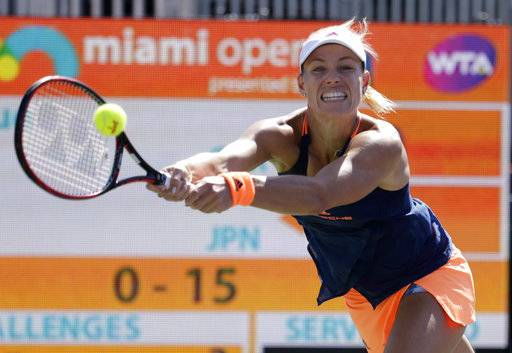 FILE - In this March 27, 2017, file photo, Angelique Kerber, of Germany, hits a return to Risa Ozaki during the Miami Open tennis tournament in Key Biscayne, Fla. Kerber is back at No. 1, replacing the pregnant Serena Williams atop the WTA rankings. Monday's May 15, 2017, move up from No. 2 represents Kerber's third stay to the top spot, for a total of 26 weeks.(AP Photo/Lynne Sladky, File)