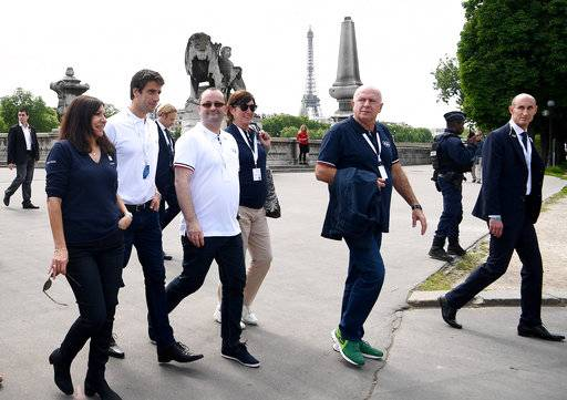 From the left, Paris mayor Anne Hidalgo, co-president of the Paris bid Tony Estanguet, president of the IOC Evaluation Commission for the 2024 Olympics Patrick Baumann walk on the bridge Alexandre III in Paris, Monday May 15, 2017. In background is the Eiffel Tower. (Franck Fife, Pool via AP)