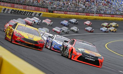 FILE - In this May 29, 2016, file photo, Martin Truex Jr (78) and Joey Logano (22) lead the field out of Turn 4 for the start of the Coca-Cola 600 NASCAR auto race at Charlotte Motor Speedway in Concord, N.C. (AP Photo/Chuck Burton)