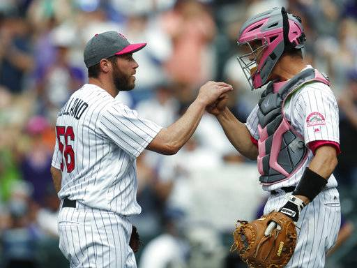 Colorado Rockies relief pitcher Greg Holland, left, is congratulated by catcher Dustin Garneau after retiring Los Angeles Dodgers' Yasiel Puig for the final out in the ninth inning of a baseball game Sunday, May 14, 2017, in Denver. The Rockies won 9-6. (AP Photo/David Zalubowski)