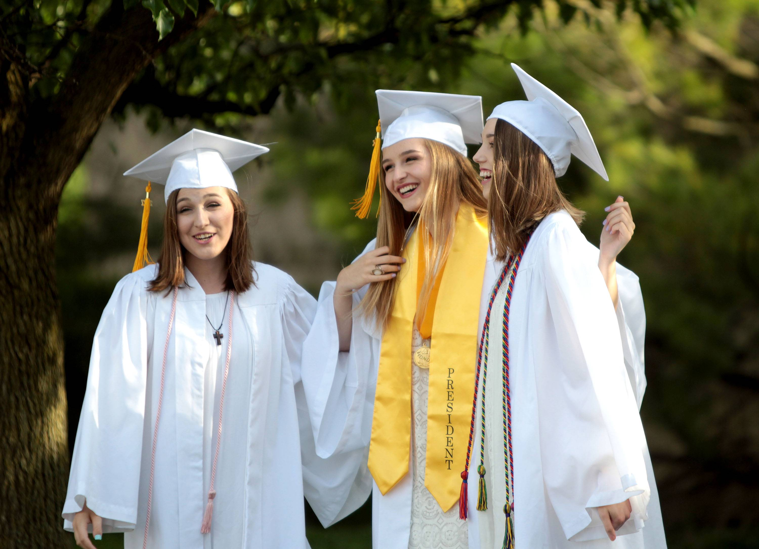 From left, Rosary High School seniors Ashley Fritz, Maggie Neff and Laney Cahill gather before the school's commencement ceremony at St. Peter Catholic Church in Geneva May 17.