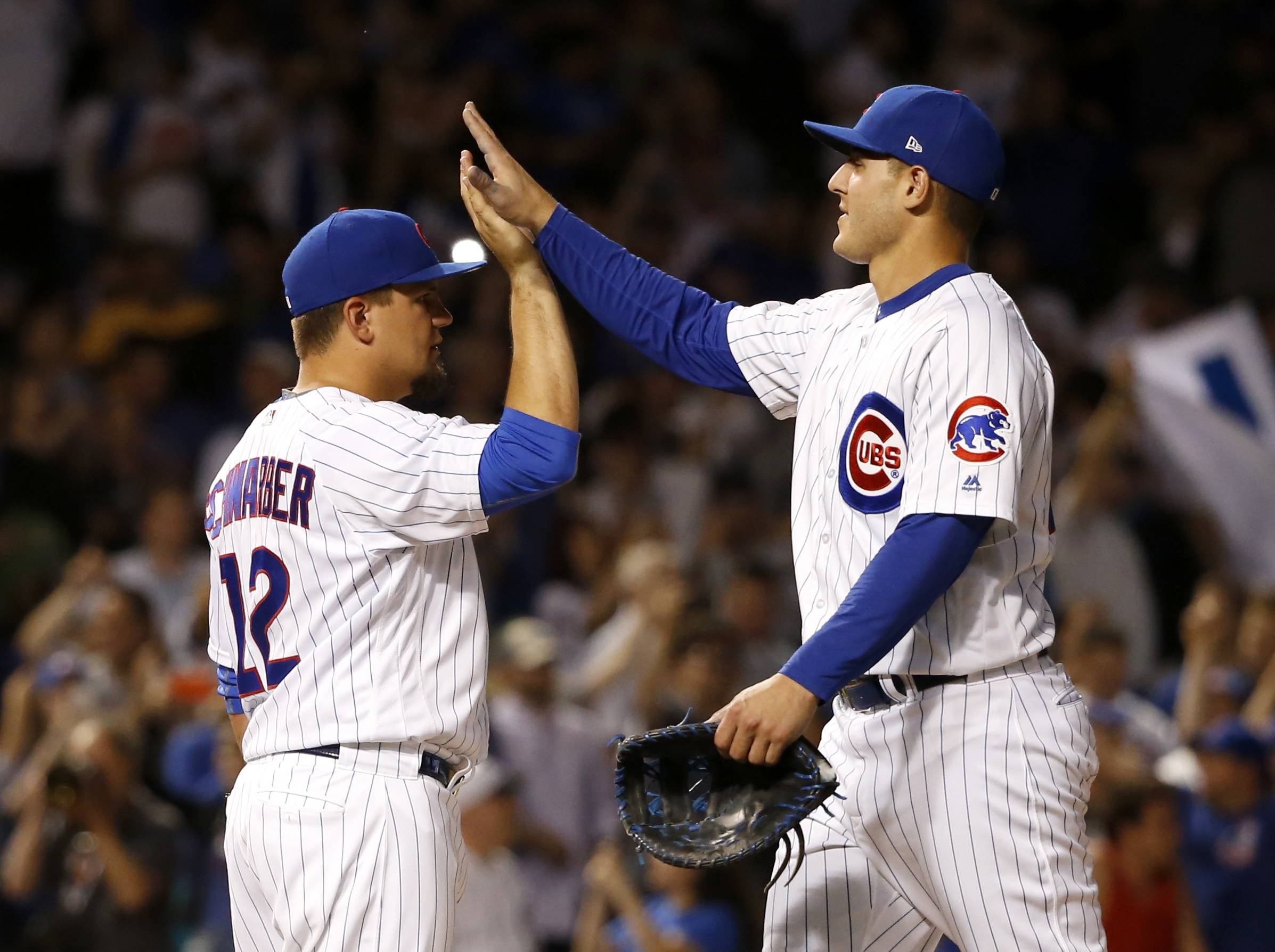 Chicago Cubs' Kyle Schwarber (12) and Anthony Rizzo celebrate the team's 7-5 win over the Cincinnati Reds in a baseball game Wednesday, May 17, 2017, in Chicago.
