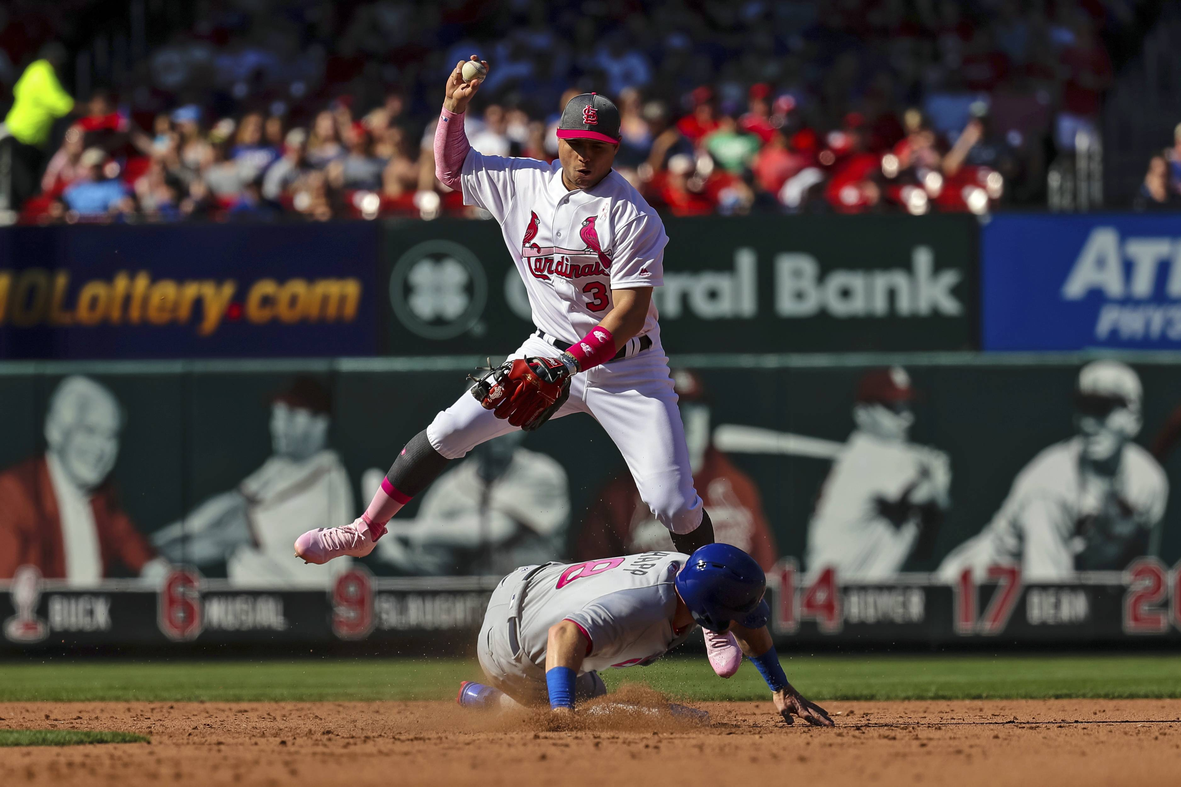 St. Louis Cardinals shortstop Aledmys Diaz, top, leaps into the air as Chicago Cubs' Ian Happ, bottom, slides in to break up a double play in the fifth inning of a baseball game, Saturday, May 13, 2017, in St. Louis. The Cubs' Anthony Rizzo was called out at first due to slide interference by Happ, (AP Photo/Tim Spyers)