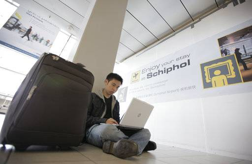 FILE - In this Saturday, April 17, 2010, file photo, a traveler from Malaysia uses his laptop computer at Schiphol Airport, Amsterdam, Netherlands. International air travelers might soon rediscover magazines, paperbacks and playing cards. Airline passengers have become hooked on their laptops and tablets to get work done or just kill time during long flights. But U.S. aviation-security officials appear determined to ban large electronic devices in the cabin of flights from Europe. (AP Photo/Peter Dejong, File)