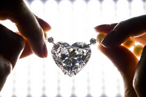 "FILE - In this Thursday, May 11, 2017 file photo, a Christie's employee displays The flawless heart-shaped Boehmer and Bassenge ""La legende"" diamond during a preview at the Christie's, in Geneva, Switzerland. A heart-shaped diamond billed as the largest of its kind to go up for auction has sold for less than the pre-sale estimate, fetching a hammer price of 13 million Swiss francs (about $13.3 million.) The sale Wednesday, May 17, 2017 capped a two-day run of high-profile jewelry auctions in Geneva. (Martial Trezzini/Keystone via AP, File)"