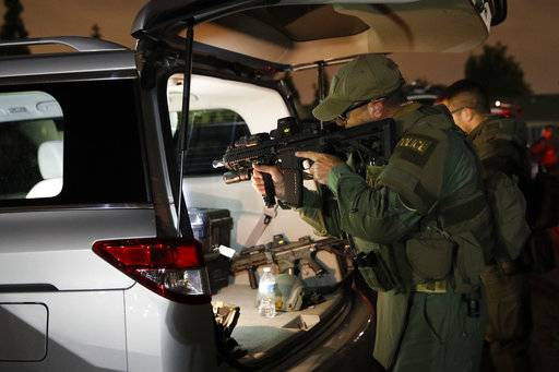 An ATF agent checks his weapon as he gets ready for a raid Wednesday morning, May 17, 2017, in Los Angeles. Hundreds of federal and local law enforcement fanned out across Los Angeles, serving arrest and search warrants as part of a three-year investigation into the violent and brutal street gang MS-13. (AP Photo/Jae C. Hong)