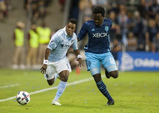 Sporting Kansas City forward Latif Blessing (9) attacks the ball past Seattle Sounders forward Seyi Adekoya (12) during an MLS soccer match Wednesday, May 17, 2017, in Kansas City, Kan. (Nick Tre. Smith/The Kansas City Star via AP)