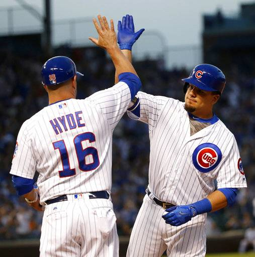Chicago Cubs' Kyle Schwarber, right, celebrates his two-run single off Cincinnati Reds starting pitcher Scott Feldman with first base coach Brandon Hyde, during the second inning of a baseball game Wednesday, May 17, 2017, in Chicago. (AP Photo/Charles Rex Arbogast)