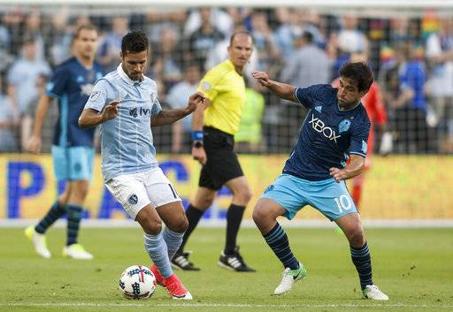 Sporting Kansas City midfielder Benny Feilhaber (10) gains the control of the ball away from Seattle Sounders midfielder Nicolas Lodeiro (10) during an MLS soccer match Wednesday, May 17, 2017, in Kansas City, Kan. (Nick Tre. Smith/The Kansas City Star via AP)