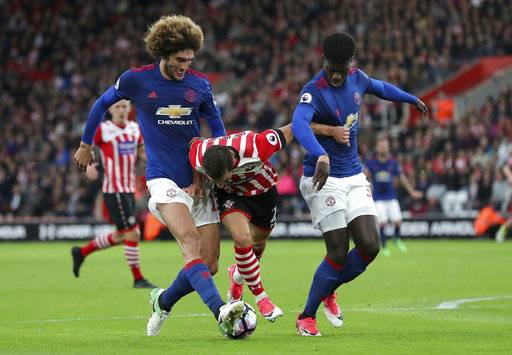 Southampton's Cedric Soares, center, fights with Manchester United's Marouane Fellaini, left, and Eric Bailly during their English Premier League soccer match at St Mary's, Southampton, England, Wednesday, May 17, 2017. (Andrew Matthews/PA via AP)
