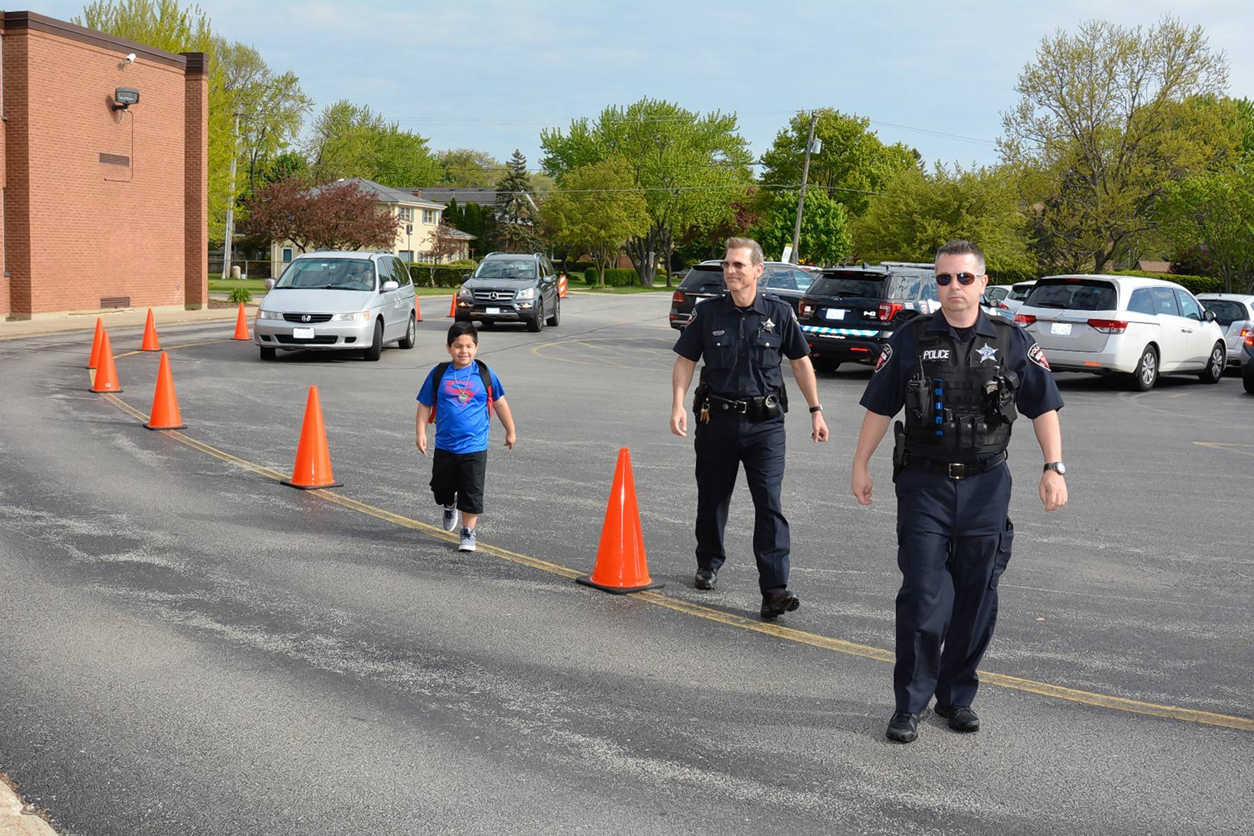 Wheeling police officers Scott Laverd and Lukasz Czapla walk into Booth Tarkington Elementary School with second grade student Leonardo Perez, who won a ride to school with police in a bingo fundraiser.