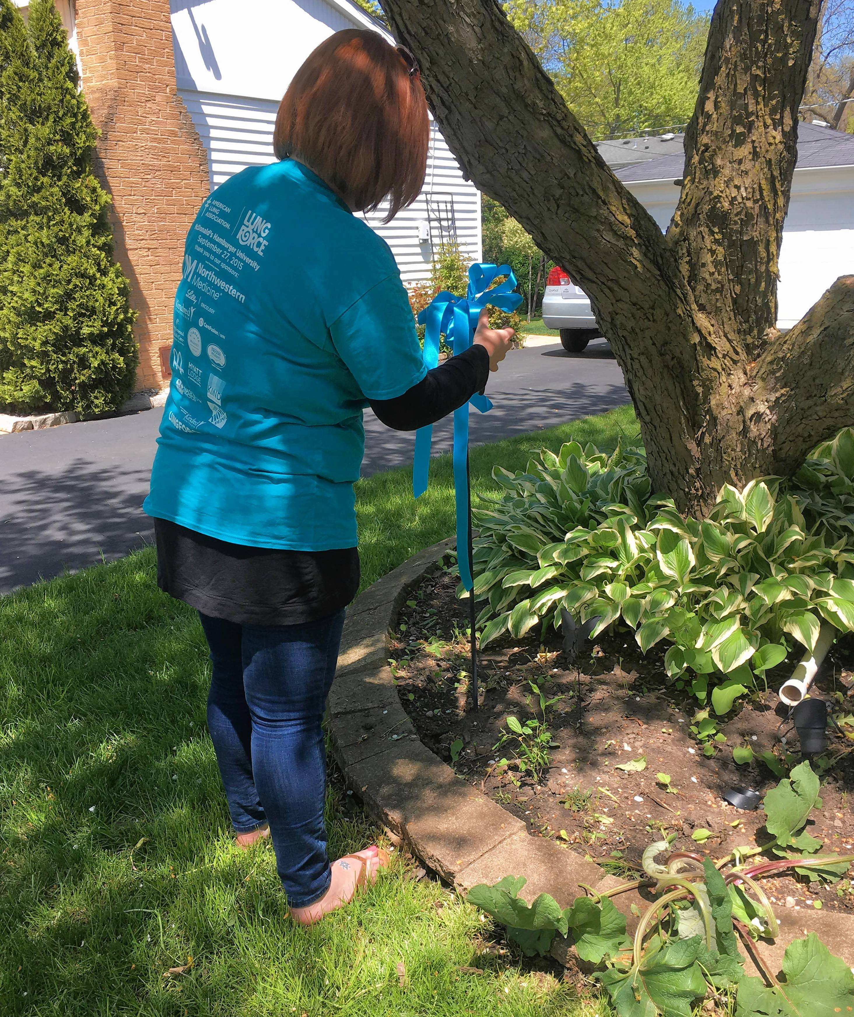 Nicole Griffin of Buffalo Grove ties ribbons on trees and mailboxes for Lung Force Turquoise Takeover last week to bring awareness of lung cancer in women. Ribbons were distributed throughout the village.
