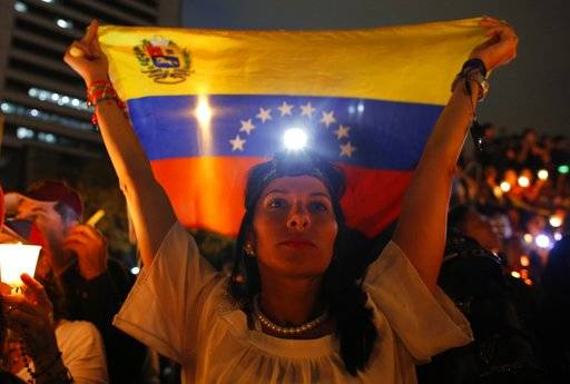 A demonstrator holds a Venezuelan flag during a vigil for the victims of the clashes with the government's security forces, during protest against President Nicolas Maduro in Caracas, Venezuela, Wednesday, May 17, 2017. Several humanitarian organizations and the opposition have accused the security forces of using too much violence during demonstrations against the government, which have left dozens dead.(AP Photo/Ariana Cubillos)