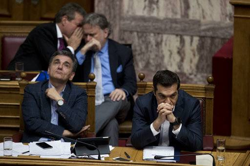 Greek Prime Minister Alexis Tsipras, right, and Finance Minister Euclid Tsakalotos, left attend a Parliament session in Athens, Thursday, May 18, 2107. Tsipras is seeking parliamentary approval for the pension cuts and further tax hikes through 2020, as part of an agreement with international bailout creditors to release the next bailout installment.(AP Photo/Petros Giannakouris)