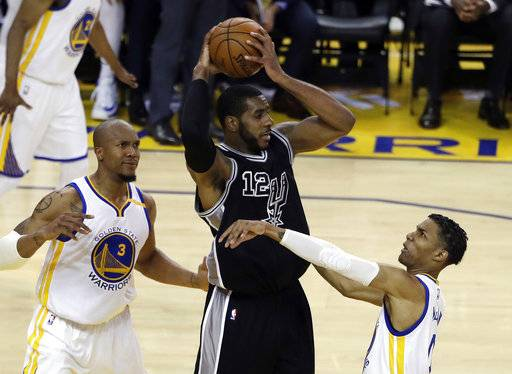 San Antonio Spurs' LaMarcus Aldridge (12) is defended by Golden State Warriors' Patrick McCaw, right, and David West (3) during the first half of Game 2 of the NBA basketball Western Conference finals, Tuesday, May 16, 2017, in Oakland, Calif. (AP Photo/Marcio Jose Sanchez)