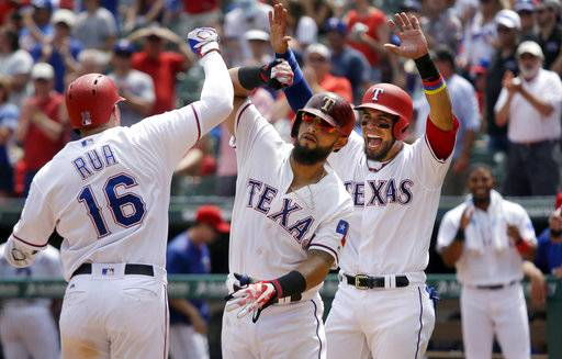 Texas Rangers Ryan Rua (16) celebrates his 3-run homer with teammates Rougned Odor, center, and Robinson Chirinos during the fifth inning of a baseball game against the Philadelphia Phillies in Arlington, Texas, Thursday, May 18, 2017. (AP Photo/LM Otero)