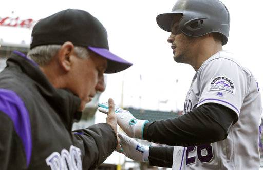 Colorado Rockies' Nolan Arenado, right, gets congratulations from manager Bud Black after his solo home run off Minnesota Twins pitcher Ervin Santana in the first inning during the first baseball game of a doubleheader, Thursday, May 18, 2017 in Minneapolis. (AP Photo/Jim Mone)