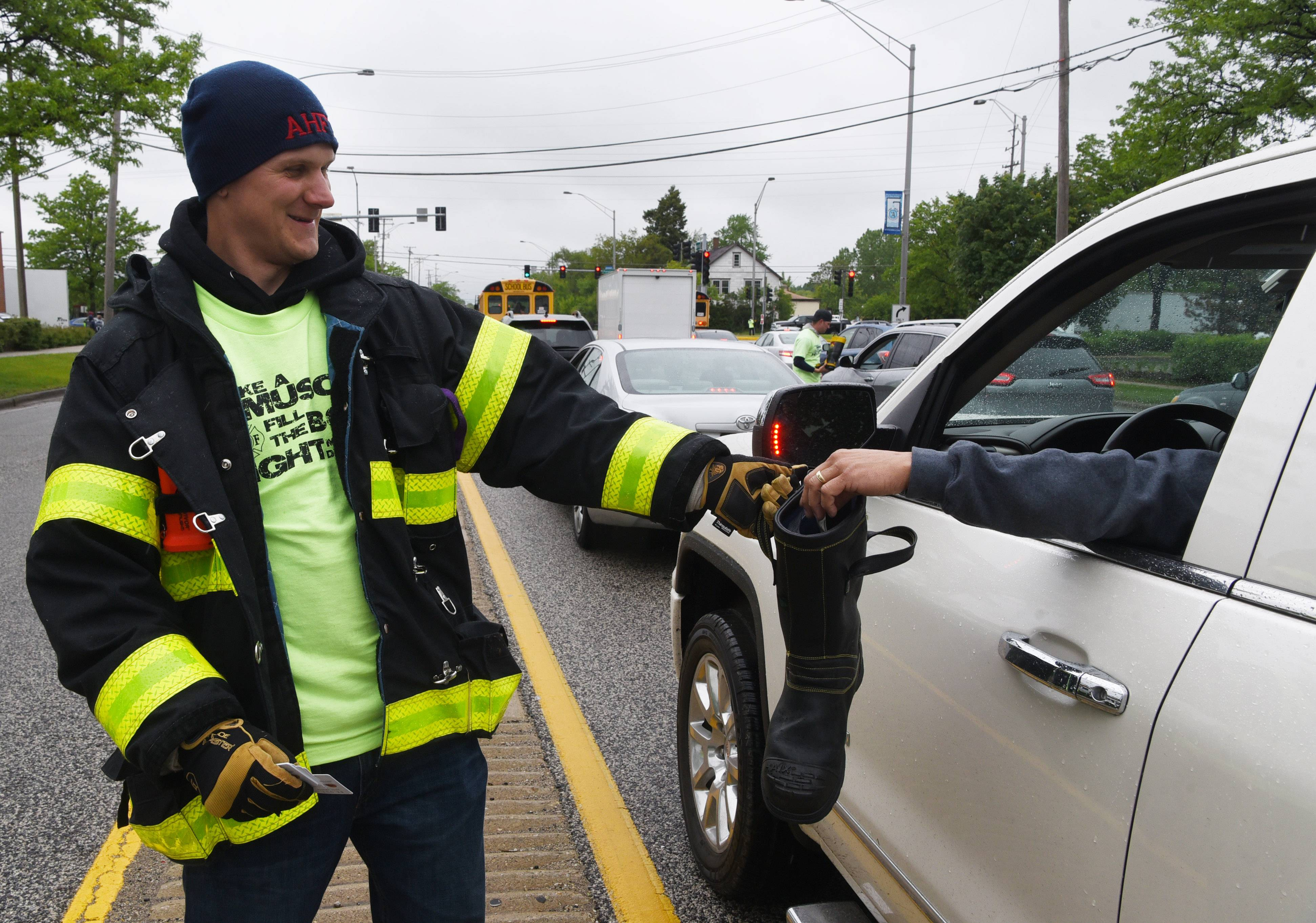 Arlington Heights firefighter/paramedic Brett Proctor of Local 3015 collects donations in a boot Friday at the intersection of Arlington Heights and Palatine roads.