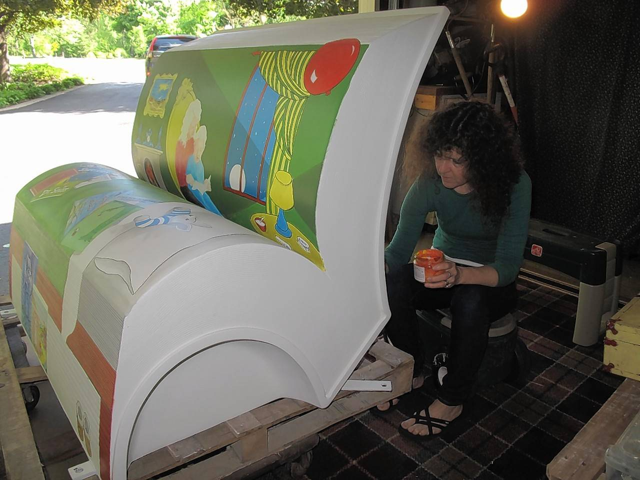 "Artist Marianne Lisson Kuhn paints the cover of ""Goodnight Moon"" onto a book bench sculpture, one of 15 that will be displayed this summer in downtown Naperville beginning Father's Day weekend."