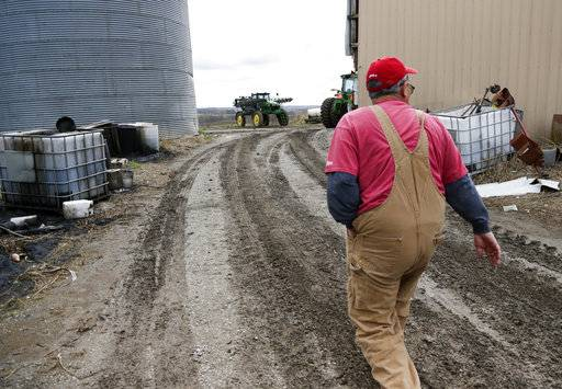 In this Tuesday, April 4, 2017, photo, Blake Hurst, a corn and soybean farmer and president of the Missouri Farm Bureau, walks to the tractor shed on his farm in Westboro, Mo. U.S. President Donald Trump has vowed to redo the North American Free Trade Agreement, but NAFTA has widened access to Mexican and Canadian markets, boosting U.S. farm exports and benefiting many farmers. Hurst says NAFTA has been good for his business and worries that he'll lose out in a renegotiation. (AP Photo/Nati Harnik)