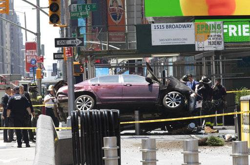 FILE - In this Thursday, May 18, 2017 file photo, a car rests on a security barrier in New York's Times Square after driving through a crowd of pedestrians, injuring at least a dozen people. A three-foot-tall piece of stainless steel in the ground ultimately stopped a speeding Honda Accord as it barreled down the crowded sidewalks of Times Square this week. In the wake of the rampage, some New Yorkers are calling for the installation of more protective bollards at the ends of city sidewalks to prevent similar incidents.