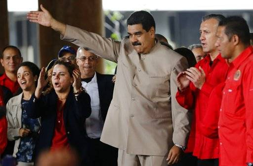 FILE - In this May 3, 2017 file photo, Venezuela's President Nicolas Maduro waves to supporters outside the National Electoral Council headquarters, in Caracas, Venezuela. The Venezuelan Foreign Ministry announced Friday, May 19, 2017, that Russian President Vladimir Putin had promised to start delivering several thousand tons of wheat after speaking on the phone with Maduro. (AP Photo/Ariana Cubillos, File)