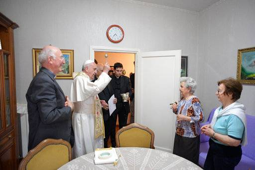 Pope Francis blesses an home during a visit to a popular neighborhood in Ostia, near Roma, where he made a surprise visit along with local priest, stopping in various homes to bless the families living there, Friday, May 19, 2017. (L'Osservatore Romano/Pool via AP)