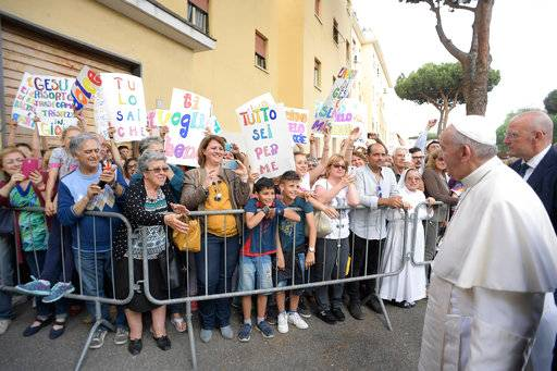 Pope Francis is welcomed by residents as he visits a popular neighborhood in Ostia, near Roma, where he made a surprise visit along with local priest, stopping in various homes to bless the families living there, Friday, May 19, 2017. (L'Osservatore Romano/Pool via AP)