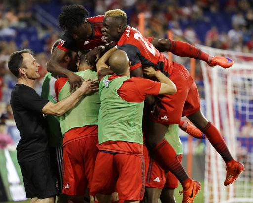 Toronto FC players mob midfielder Benoit Cheyrou, not visible, after he scored a goal on the New York Red Bulls during the second half of an MLS soccer match, Friday, May 19, 2017, in Harrison, N.J.