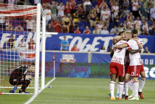 New York Red Bulls players celebrate a goal by Bradley Wright-Phillips (99) as Toronto FC goalkeeper Alex Bono, left, is slow to get up inside the net during the first half of an MLS soccer match, Friday, May 19, 2017, in Harrison, N.J.