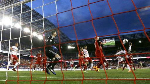 New York Red Bulls forward Bradley Wright-Phillips (99) kicks over his head while scoring a goal on Toronto FC goalkeeper Alex Bono (25) during the first half of an MLS soccer match, Friday, May 19, 2017, in Harrison, N.J.