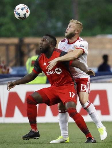 Toronto FC forward Jozy Altidore, left, tries to control the ball as New York Red Bulls forward Mike Grella (13) defends during the first half of an MLS soccer match, Friday, May 19, 2017, in Harrison, N.J.