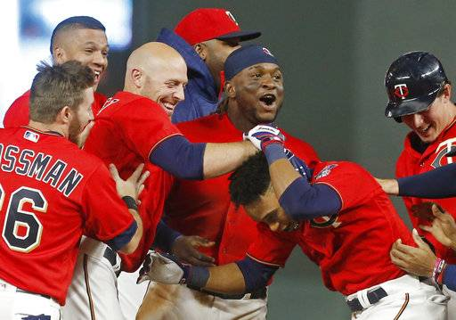 Minnesota Twins' Jorge Polanco, right, is swarmed by teammates after his walk-off sacrifice fly in the 10th inning of a baseball game against the Kansas City Royals on Friday, May 19, 2017, in Minneapolis. The Twins won 4-3.