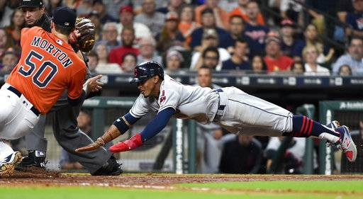 Cleveland Indians' Francisco Lindor, right, attempts to score past Houston Astros starting pitcher Charlie Morton (50) during the fifth inning of a baseball game, Friday, May 19, 2017, in Houston. Lindor was tagged out by Morton on the play.