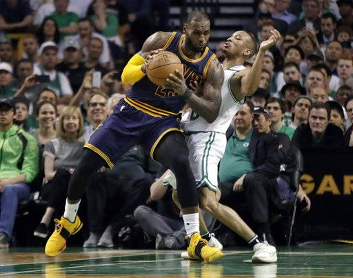 Cleveland Cavaliers forward LeBron James, left, muscles his way to the basket as Boston Celtics guard Avery Bradley, right, tries to defend during first half of Game 2 of the NBA basketball Eastern Conference finals, Friday, May 19, 2017, in Boston.