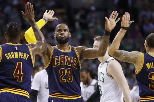 Cleveland Cavaliers forward LeBron James trades high-fives with teammates Iman Shumpert, left, and Deron Williams, right, during the first half of Game 2 of the NBA basketball Eastern Conference finals against the Boston Celtics, Friday, May 19, 2017, in Boston.