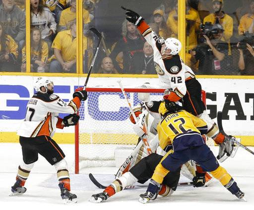 Anaheim Ducks defenseman Josh Manson (42) jumps over Nashville Predators center Mike Fisher (12) to swat the puck away during the third period in Game 4 of the Western Conference final in the NHL hockey Stanley Cup playoffs Thursday, May 18, 2017, in Nashville, Tenn. At left is Ducks center Ryan Kesler (17).
