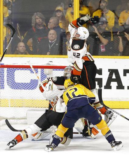 Anaheim Ducks defenseman Josh Manson (42) jumps over Nashville Predators center Mike Fisher (12) to swat the puck away during the third period in Game 4 of the Western Conference final in the NHL hockey Stanley Cup playoffs Thursday, May 18, 2017, in Nashville, Tenn.