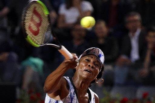Venus Williams, of the United States, returns the ball during a quarter finals match against Spain's Garbine Muguruza at the Italian Open tennis tournament, in Rome, Friday, May 19, 2017.