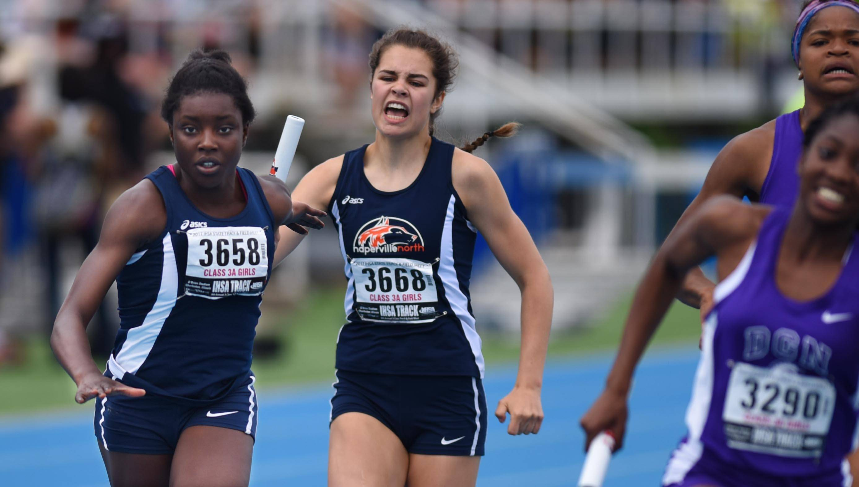 Naperville North's Allison Grady yells and hands the baton to teammate Saffilla Allie in the Class 3A 4x200-Meter Relay at the state girls track and field meet finals on Saturday at Eastern Illinois University in Charleston.