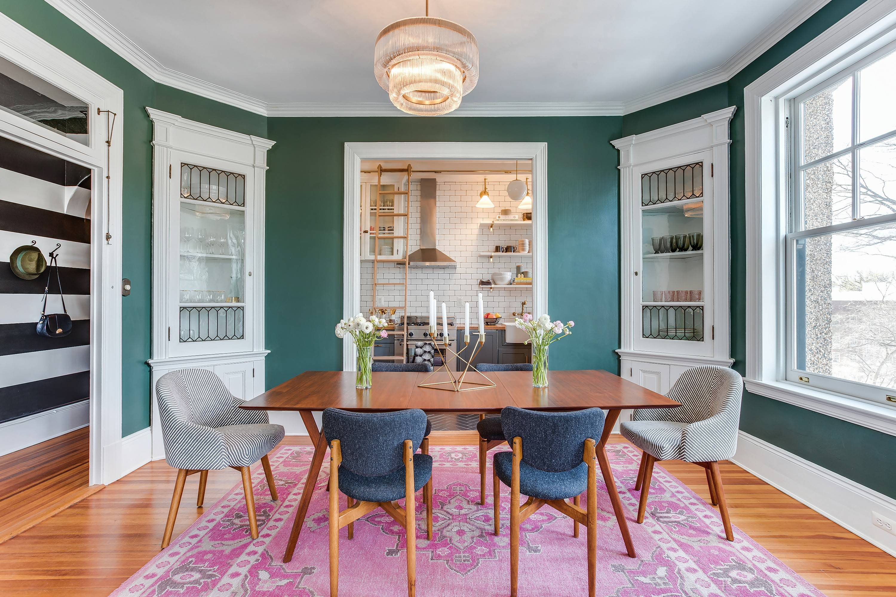 The dining room in Louisa Bargeron's apartment in Washington, D.C., retains two original corner cabinets with leaded glass. The walls were painted a warm green.