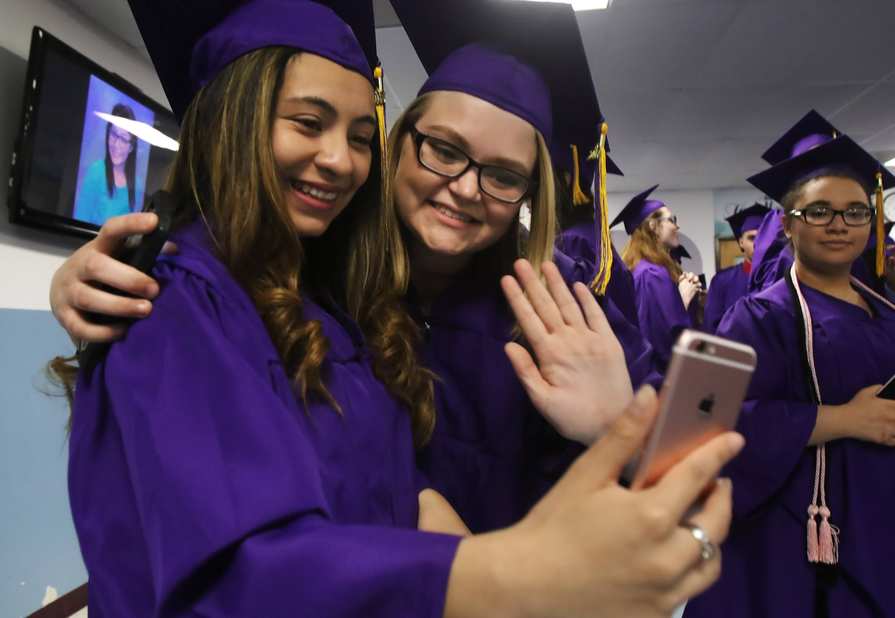 Ariela Solano, left, and Josephine Karg wave to friends during FaceTime on their phone before the Wauconda High School graduation Sunday at Quentin Road Bible Church in Lake Zurich. There were 317 seniors who received their diploma at the commencement exercises.